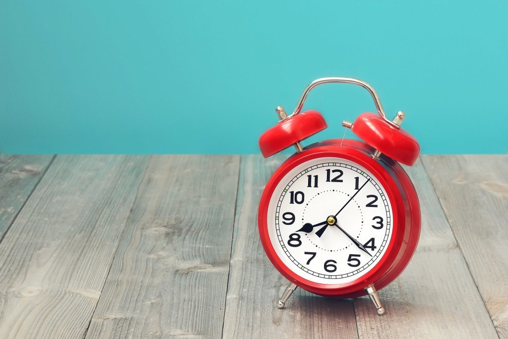 Red retro alarm clock on a wooden table on a blue background. The sound of the alarm.