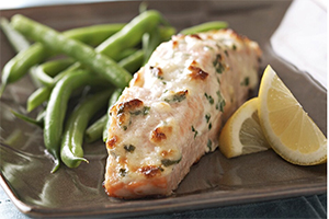 parmesan baked salmon with string beans and a lemon wedge on a plate