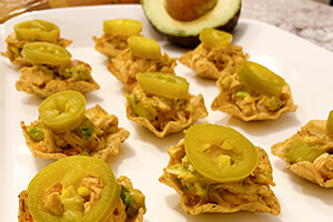 mini chicken taco bites on a plate served with avocado and topped with sliced jalapeno peppers