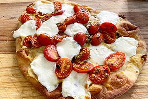 a flatbread pizza with cut up tomatoes, melted cheese and hummus spread