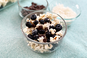 a bowl of popcorn with blueberries, toasted coconut and chocolate chips